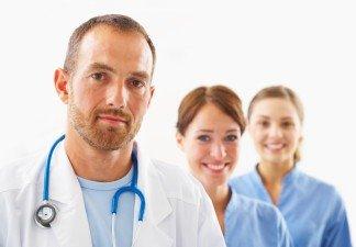 Medico en el frente y 2 médicas sonriendo detrás
